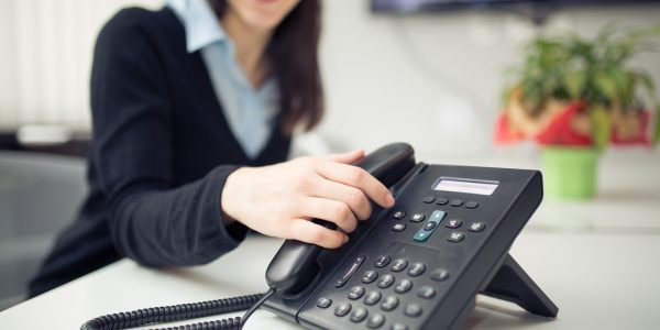 The benefits of SIP trunking help a businesswoman using a phone line