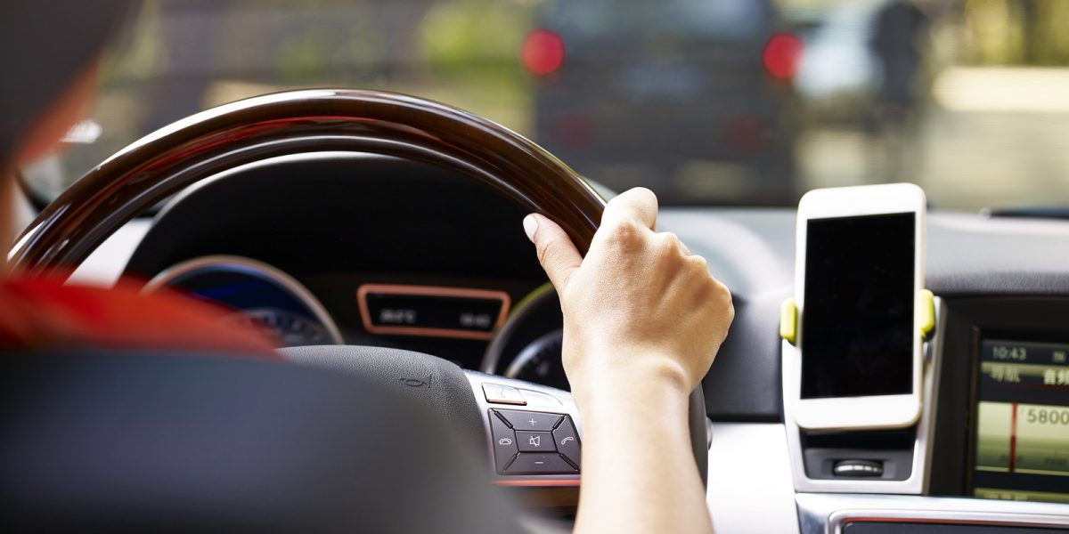Rear view of a car driver with a dashboard-mounted smartphone using a communication platform