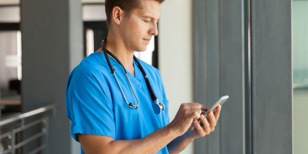 A healthcare professional uses SMS solutions for business to communicate with patients