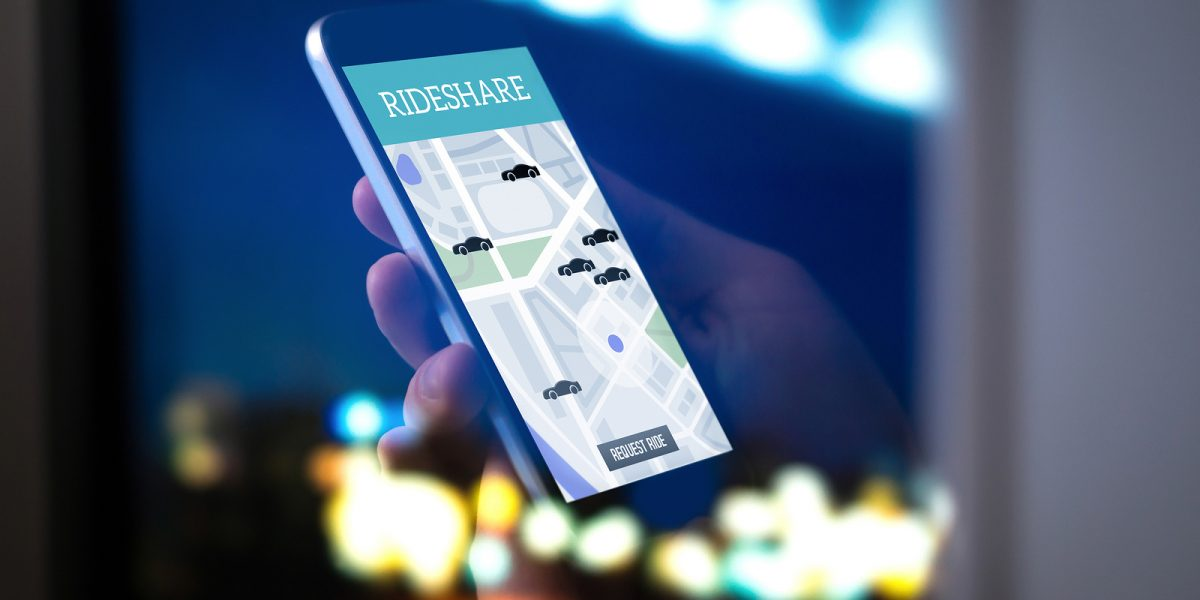 A hand holding a mobile phone and using a ride-hailing app powered by CPaaS solutions