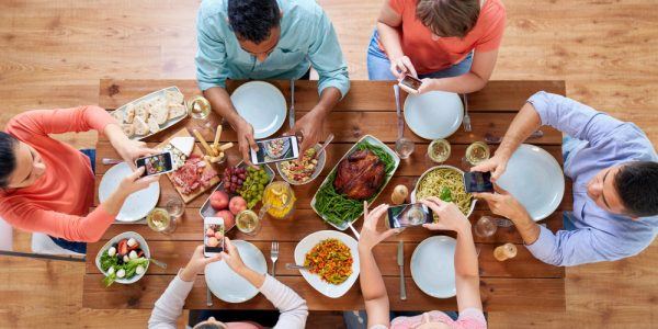 People eating Thanksgiving dinner use communication technology to take pictures and share the moment.